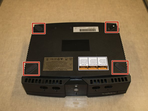 Turn the Xbox on its back and remove the rubber feet in each corner using a flathead screwdriver.