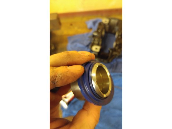 Image 1/3: Put a bit of assembly lube on the piston and slowly but firmly insert the piston into the proper hole until seated all the way in. The pistons are different sizes on this model, so be aware of the difference and placement in the proper area.