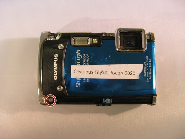 "Image 1/3: Using a T6 Torx screwdriver, unscrew the two 3.5mm screws located on the black ""Olympus"" face plate."