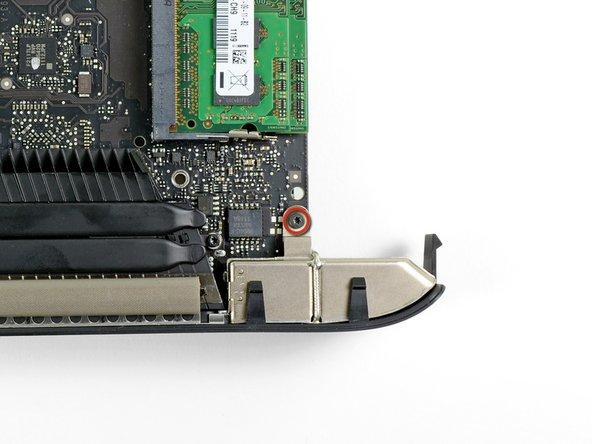 Entferne die einzelne 2,6 mm Torx T6 Schraube, welche die I/O Blende in der Nähe des RAM am Logic Board befestigt.