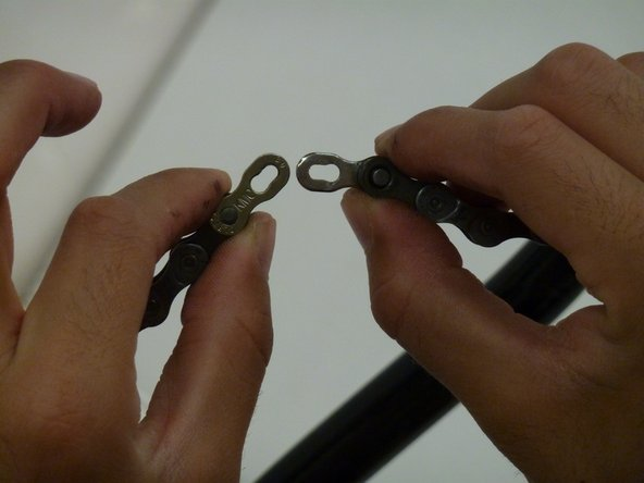 With pliers squeeze the two pins together so that the chain comes apart.