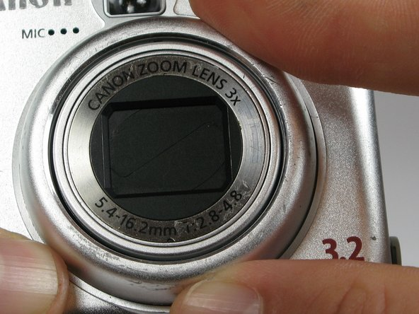 On the front of the camera, press the button on the lower left of the lens.