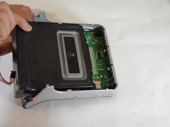 Slide the speaker towards the bottom of the device to remove.