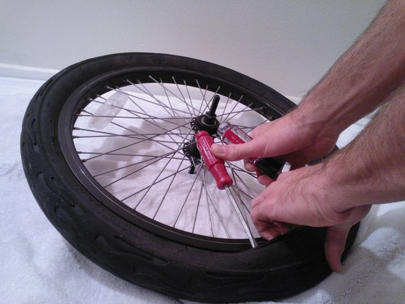 Place your fingers in between where the tire is already overlapping the rim and pry out the rest of the tire so that the whole tire overlaps the rim.