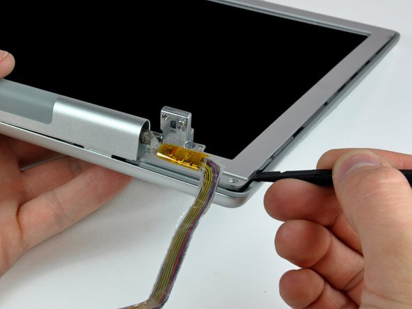 Image 2/2: Pry the rear bezel away from the front bezel to slightly separate the bottom edge of the rear display bezel.