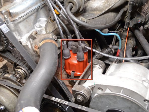 The distributor cap is located next to the engine and has all of the spark plug wires connecting to it.