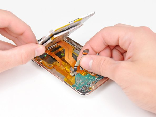 Image 1/1: Peel the display data cable off the adhesive securing it to the rear panel.