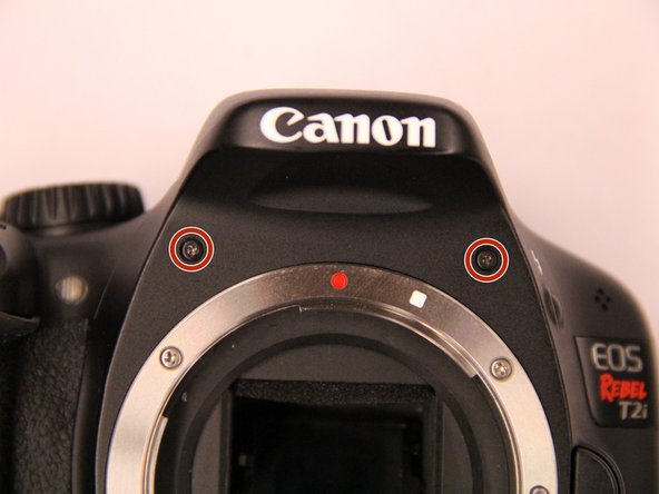 Remove the two black screws on the front of the camera just above the lens mounting ring.
