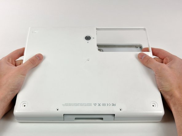 Image 1/1: Turn the computer so that the back is facing you and pull the lower case up and toward you until the back tabs pop free.