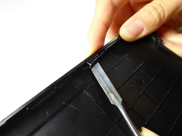 Using a metal spudger and/or your fingers, press the power button in and lift the outside tab.