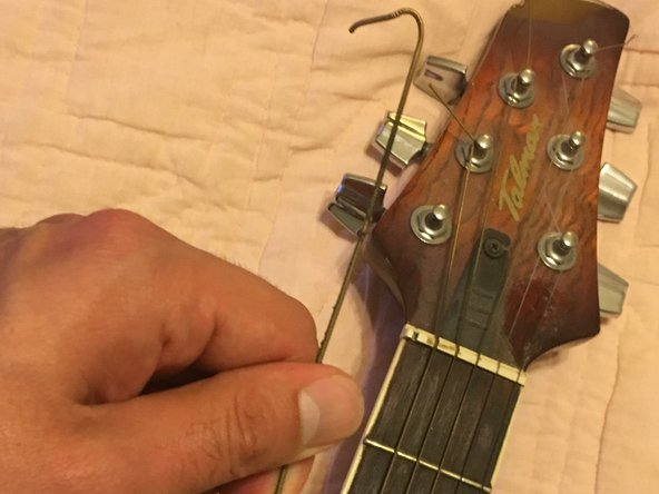 Carefully unwind the guitar string from the tuning machine and then repeat this step for the other five strings.