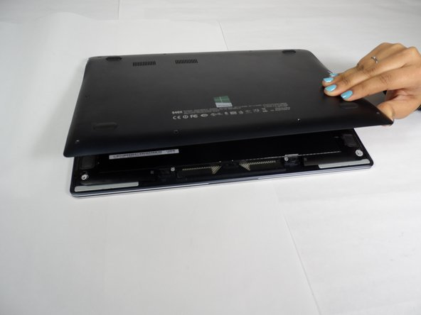 Image 3/3: Carefully remove the bottom case of the laptop to reveal the damaged speakers.