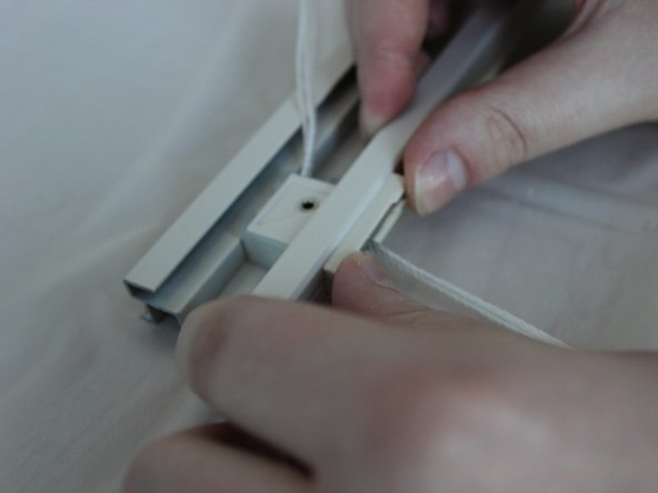 Insert the cord lock into the gap in the top rail with the opaque plastic side facing up.