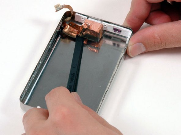 Slide a spudger beneath the orange headphone jack cable and use it to pry the cable up from the rear panel.