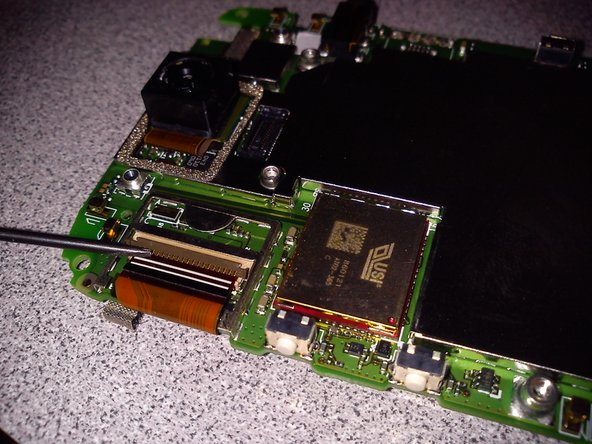 Image 1/2: Once the plastic flipper has been flipped, slowly nudge the flex cable out of the socket.