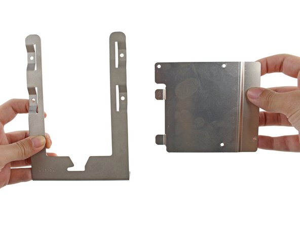 Insert the two tabs on the left side of the metal adapter bracket into the slots on the left side of the hard drive bay sled.