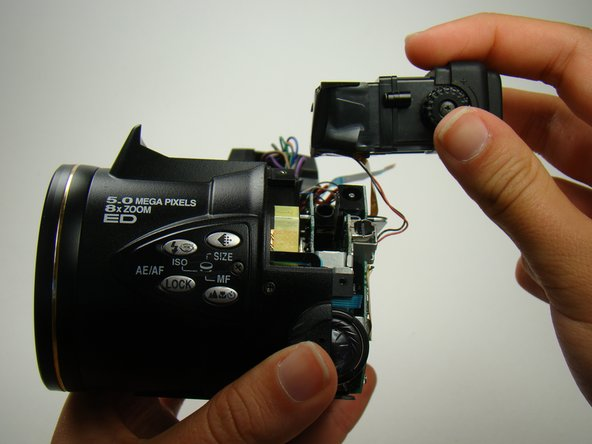 Image 1/3: Unplug the orange ribbon wire from the body of the camera.