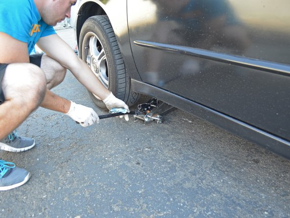 Image 2/2: Slowly lower the jack until the car no longer rests on it. Then remove the jack from underneath the car.