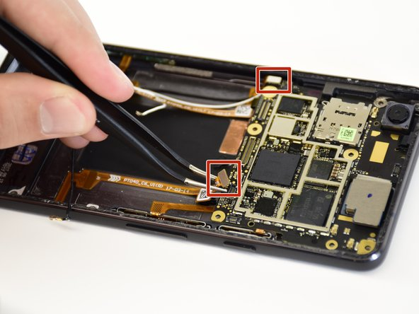 Remove the two gold ribbon connectors by grabbing them, one at a time, with tweezers and lifting up.