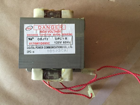 "The transformer is labeled ""Danger High Voltage"" in red letters, and will be already disconnected from the oven's bottom grate which was removed in steps 4 and 5."