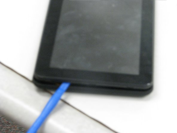Use the iFixit plastic opening tool to pry open the back of the tablet.
