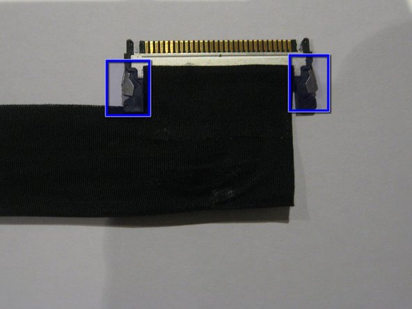 Image 2/2: Press '''IN''' the 2 silver spring loaded catches on either side to release the cable and gently extract it from the connector