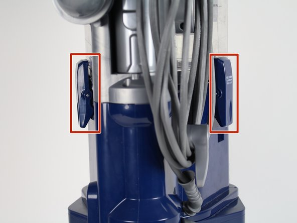 Locate the latches on the side of the dust cup, the clear plastic chamber in the center of the vacuum.