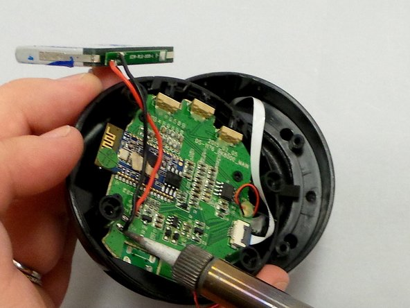 Image 1/2: Using a soldering iron desolder the wires from the motherboard.