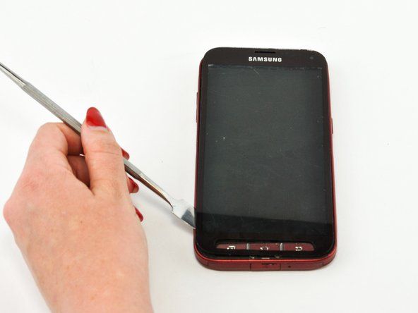 Using a plastic opening tool or spudger, pry up the screen after the adhesive has melted.