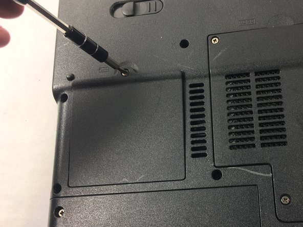 Image 1/2: Loosen and remove the single screw at the top of the RAM's cover plate.