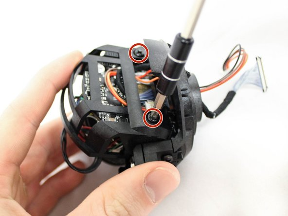 Gently tilt the camera forward in the cradle of the camera housing to get access to the two 10m screws.