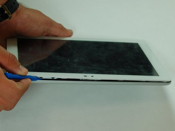 Image 1/2: Use a plastic opening tool to remove the rear panel from the front case.