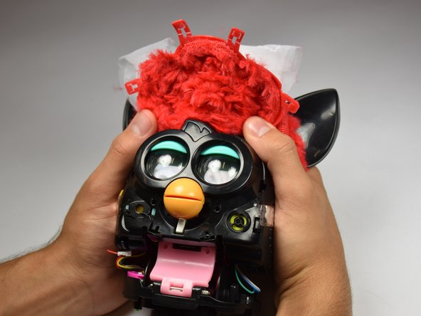 Lift up on the fur covering until the face of the Furby is exposed.