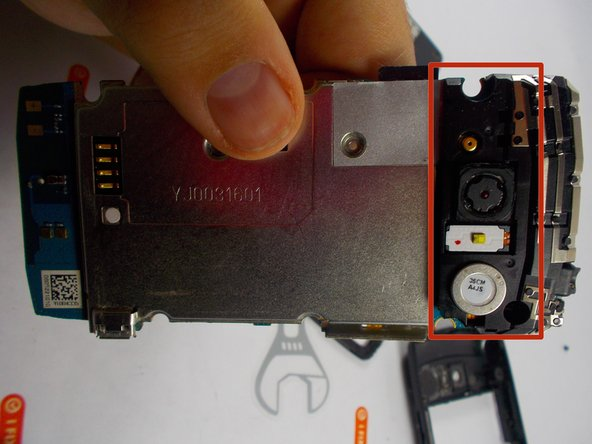 Flip phone over, and notice where the camera lies on the other side, there are three small clips connecting a black casing over the section of the phone. Gently using your hands or the prying tool, take these clips off.