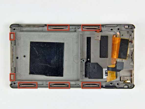 Image 1/2: The five plastic clips along the side of the Zune lock onto small aluminum tabs cast into the inner chassis. To separate these clips, the plastic portion must be pushed toward the inside of the Zune while prying the inner chassis up off the front case.