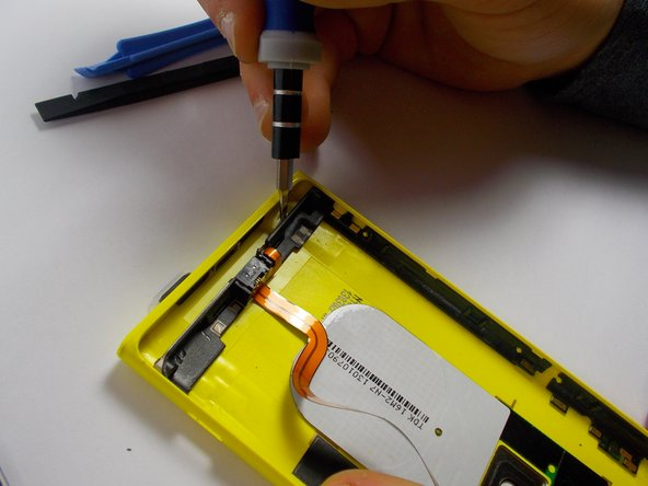 Image 2/3: Once you have one side clearly separated from the shell of the phone, put the screwdriver in the opening you have created and push the whole piece away from its shell.