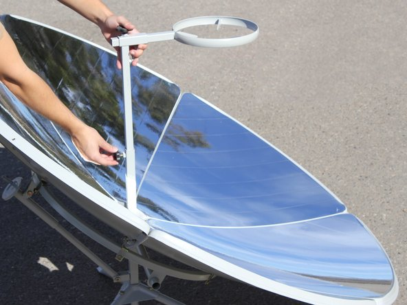 Stand the solar cooker upright on the tripod stand and attach the cooker ring stand to the cross bar coming through the center of the solar panel dish.