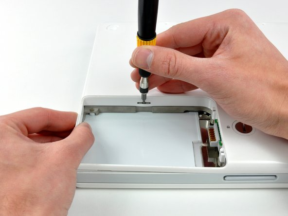 There is a slot on the wall of the battery compartment that locks the lower case in place. Use a small flathead screwdriver to pry out the slot's lower rim and pull up on the lower case to free the slot from the tabs holding it.