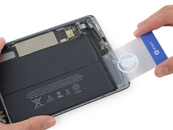 Remove the plastic card and insert it under the cell nearest the edge of the case.