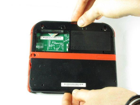 Die Rückabdeckung ist mit einem Flachbandkabel an der Hauptplatine verbunden. Entferne sie deswegen nicht zu weit vom Gerät.
