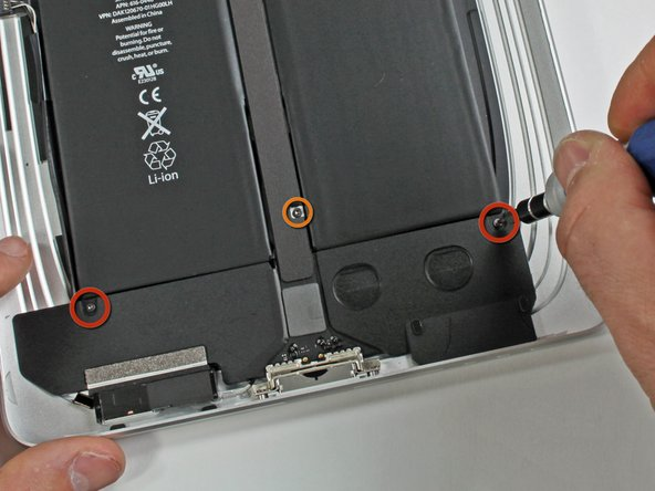 Image 1/1: Remove the single T5 Torx screw securing the middle of the dock cable to the rear panel assembly.
