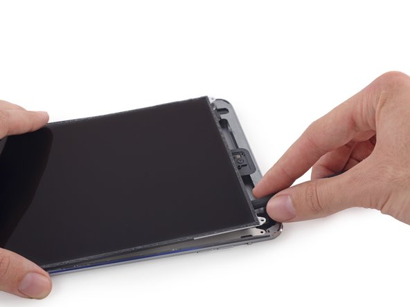 Image 2/3: Insert the spudger between the LCD and LCD shield plate and slide it to the far edge of the iPad.