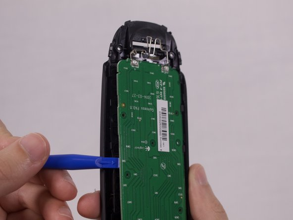 Use the plastic opening tool to remove the motherboard.
