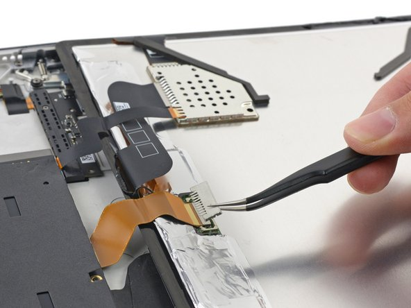Image 1/2: Right away, we notice two cables tethering the display to the motherboard. ''Fortunately'', they're conveniently located along one edge—meaning we really ''can'' flip this thing open like a book—and we easily dispatch their press-on connectors.