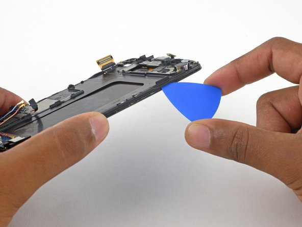 Insert an opening pick on the right side of the phone between the display assembly and plastic display frame.