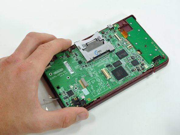 Image 1/2: The motherboard cannot be completely removed yet. It is still attached by the upper LCD's display data ribbon cable.