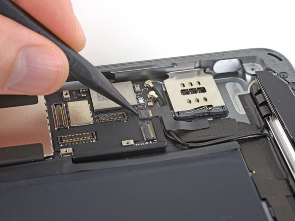 Use the pointed end of a spudger to flip up the retaining flap on the SIM board cable connector.