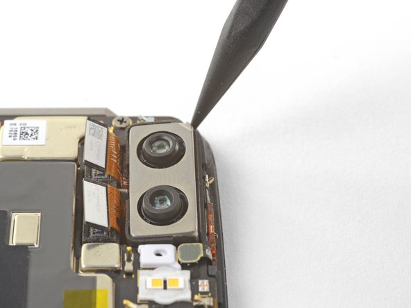Insert the point of a spudger under the top left corner of the camera module and pry up to loosen it from its recess.