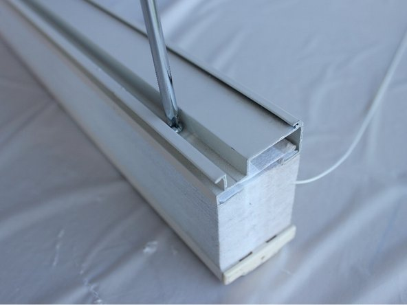Use the phillips screwdriver to put the screw back into the top rail.