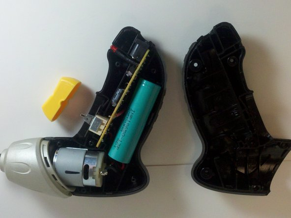 Image 3/3: Remove battery casing half to expose screwdriver internals.